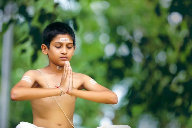 The indian priest child doing meditation