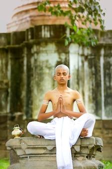 公園でヨガをしているインドの司祭の子供