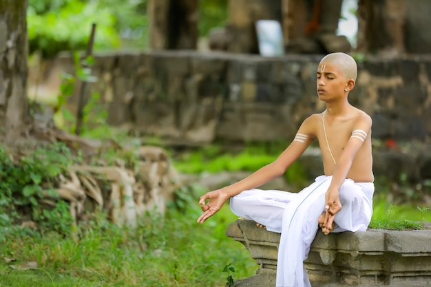Indian priest child doing yoga at park
