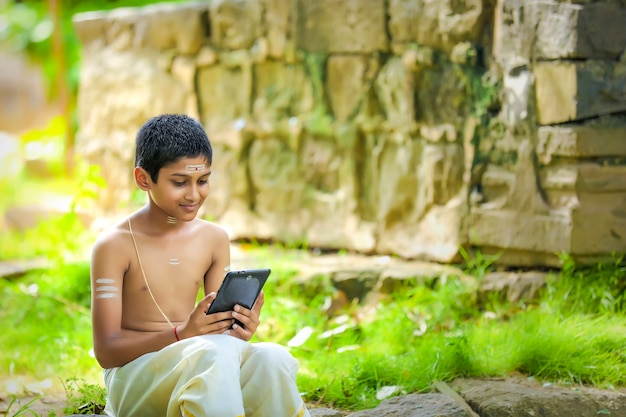 The indian priest child using smartphone