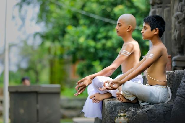 公園でヨガをしているインドの司祭の子供たち