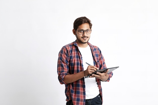 Indian professional designer using graphic tablet connected to smartphone with digital pen