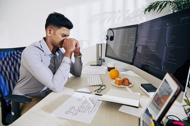 プログラミングコードに取り組んでいるときに解決策を見つけようと懸命に努力しているインドのプログラマー
