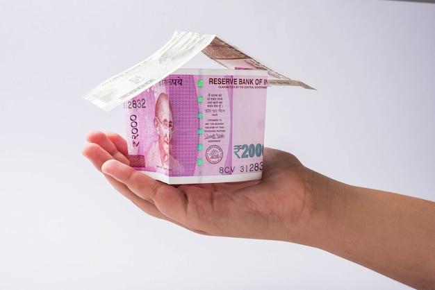인도 부동산 비즈니스 개념은 화려한 배경 위에 격리된 종이 화폐 메모를 사용하여 만든 3d 모델 홈을 보여줍니다. 선택적 초점