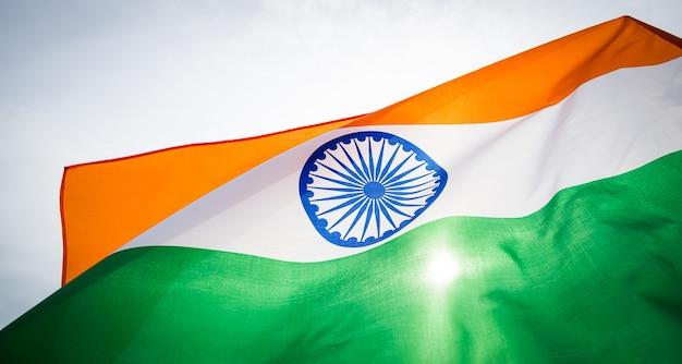 インド共和国記念日のコンセプト。空の背景にインドの旗を持っている手。