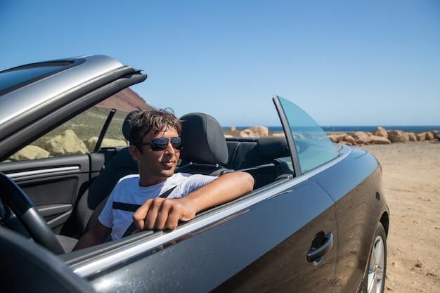 컨버터블 자동차에 앉아 있는 인도 부자는 선글라스를 끼고 옆을 바라보고 있다. 비싼 차에 앉아 깨달은 남자. 인도 민족의 40세 사람.