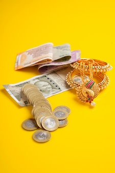 Indian rupees note, coins and gold jewelry over yellow surface
