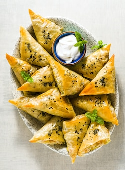 フィロをスパイシーなジャガイモと野菜で作ったインドのサモサ。ヨーグルト、ミント、レモンを添えてください。広告のためにクローズアップ