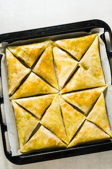 Indian samosa made with phyllo with spicy potatoes and vegetables on a baking sheet, ready to be baked in the oven with black sesame seeds