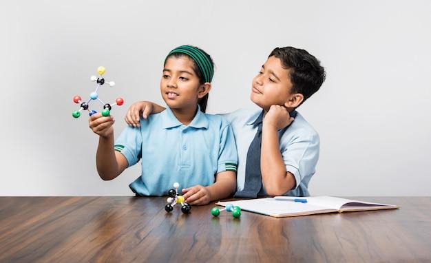 물리학, 선택적 초점을 연구하기 위해 분자 모델 키트를 사용하여 제복을 입은 인도 학교 소년과 소녀 또는 과학 학생