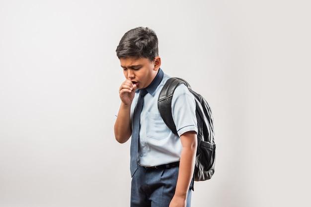 흰색 배경에 격리된 교복과 책가방을 입고 기침하는 인도 학교 소년