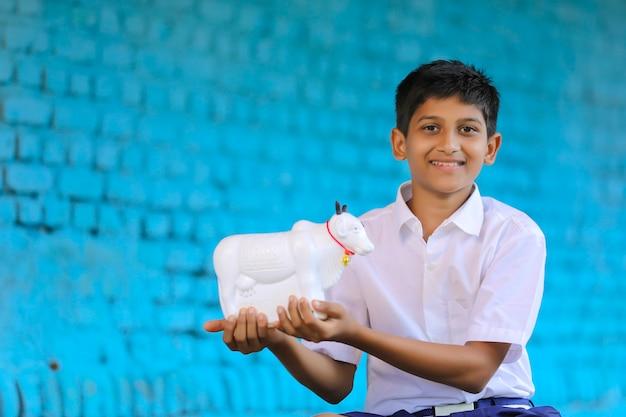 소 모양의 돼지 저금통을 손에 들고 있는 인도 학교 소년