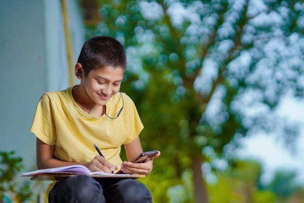 モバイルアプリケーションを使用して電話遠隔教育クラスを開催し、オンラインレッスンを視聴し、アプリでビデオ通話を行い、自宅で勉強するメモを作成するインドの男子生徒