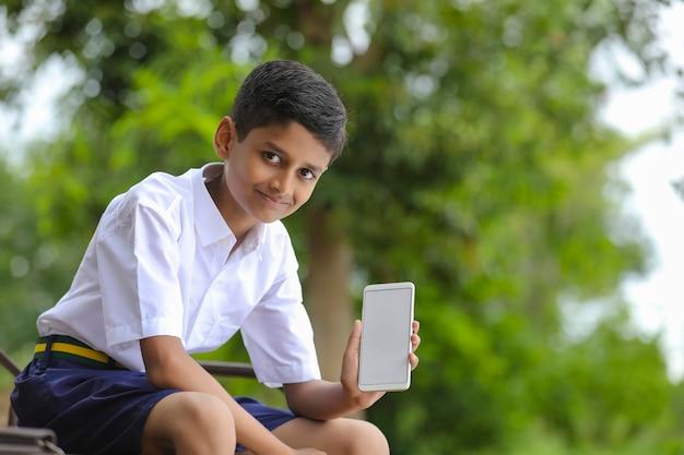 Indian school boy showing smartphone screen. online education concept.