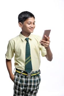 Indian school boy using smartphone. online education concept.