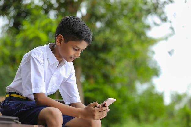 Indian school boy using smartphone screen. online education concept.