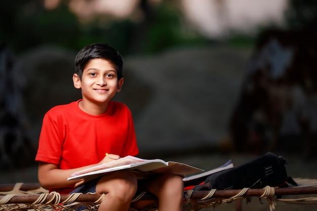 ノートブックと自宅で勉強しているインドの男子生徒