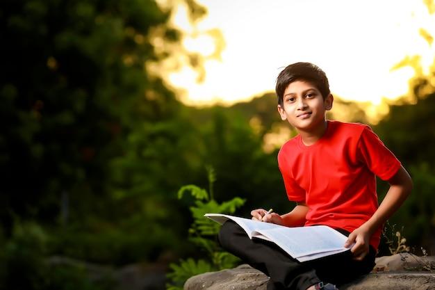 Индийский школьник с записной книжкой и учится дома