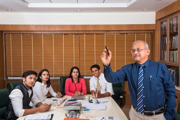 インドのシニアビジネスマンが会議室でプレゼンテーションを行うマーカーペンで透明なガラスの上に書いている間、バックグラウンドで他の若いビジネスマン
