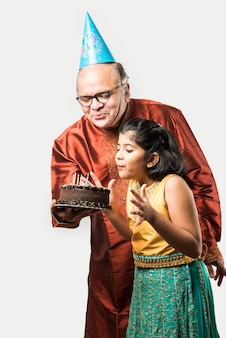 Indian senior or old man with granddaughter celebrating birthday by blowing candles on cake while wearing ethnic wear, standing isolated against white background
