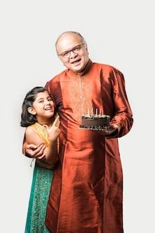 Индийский старший или старик с внучкой празднует день рождения, задувая свечи на торте в этнической одежде, стоя изолированно на белом фоне