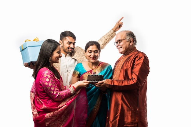 Indian senior woman with family celebrating birthday by blowing candles on cake while wearing ethnic wear