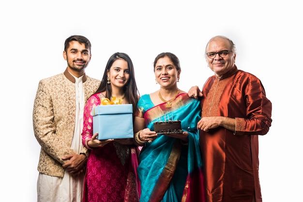 エスニックウェアを身に着けている間ケーキにろうそくを吹くことによって誕生日を祝う家族とインドの年配の女性