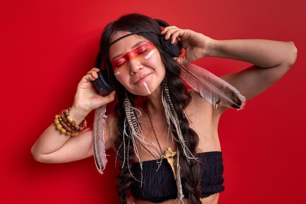 Indian shaman woman listening to music in wireless headphones, enjoying modern technologies