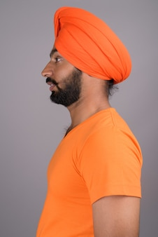 Indian sikh man wearing turban and orange shirt