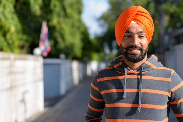 Indian sikh man wearing turban in the streets outdoors while smiling