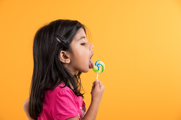 Индийская маленькая девочка с леденцом или леденцом, азиатская девушка и леденец или леденец, игривая индийская милая девушка позирует с леденцом или конфетой
