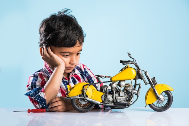 Indian small kid playing or repairing a toy motor bike or minibike