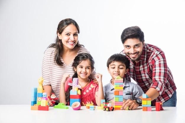 흰색 배경에 대해 젊은 부모와 함께 다채로운 블록 장난감을 재생 인도 작은 아이
