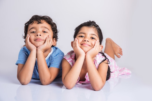 포옹 인도 작은 형제 자매, 2 인도 아이의 초상화, 인도 작은 소년과 흰색 배경 위에 서로 가까이 앉아 작은 소녀, 쾌활한 인도 소년과 소녀 사진을 위해 포즈를 취하는