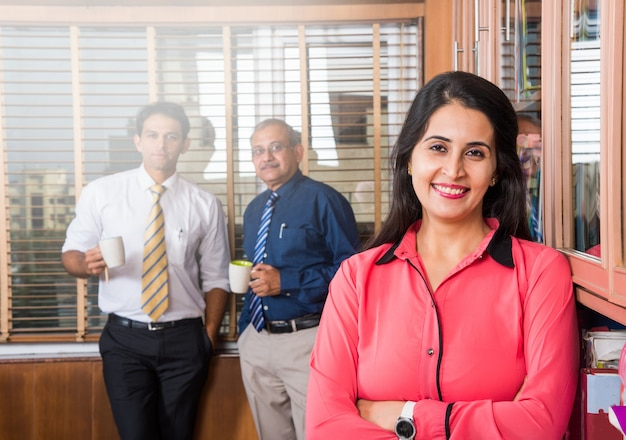 Индийская умная бизнес-леди стоит со скрещенными руками, в то время как 2 других деловых человека пьют кофе и обсуждают на заднем плане