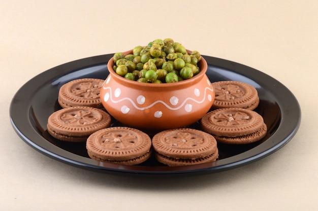 インドのおやつ:プレートにクリームビスケットとスパイスで揚げたグリーンピース(チャタパマタル)。