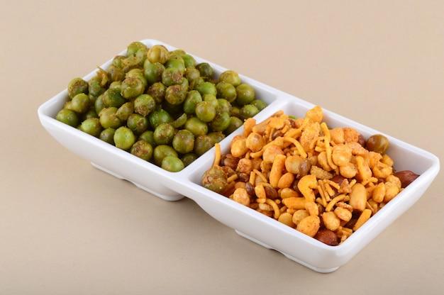 Индийская закуска: смесь со специями и жареный зеленый горошек {чатпата матар} в белой тарелке.