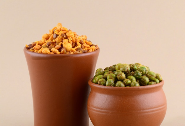 Indian snack: mixture and spiced fried green peas {chatpata matar} in clay pots.