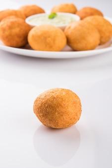 インドのスナックaloobondaまたはbatatavadaまたはuraddaalvadaまたはpakodaまたはpakora。緑のチャツネを添えて。セレクティブフォーカス
