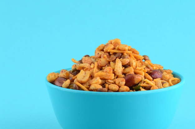 Indian snacks : mixture (roasted nuts with salt pepper masala, pulses, channa masala dal green peas) in blue bowl in