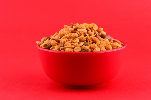 Indian snacks : mixture (roasted nuts with salt pepper masala, pulses, channa masala dal, green peas) in red bowl on red background