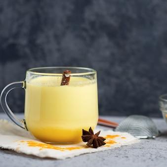 Indian spice turmeric golden milk in a mug on a dark stone table