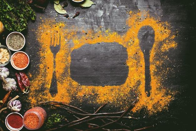 インドのスパイスとハーブ。テーブルに挽いたスパイスをプリント。黒い黒板に。