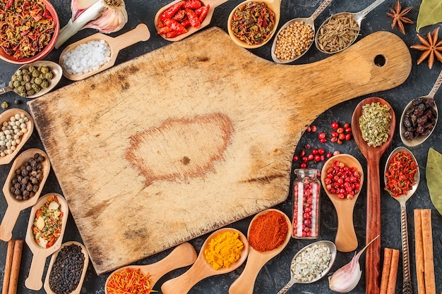 Indian spices, herbs and empty cutting board on black