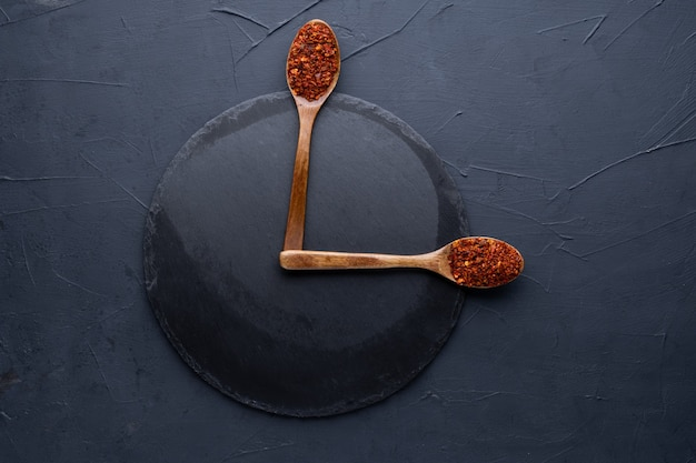 Indian spices selection in wooden spoons over dark cement background. food or spicy cooking concept, healthy eating background
