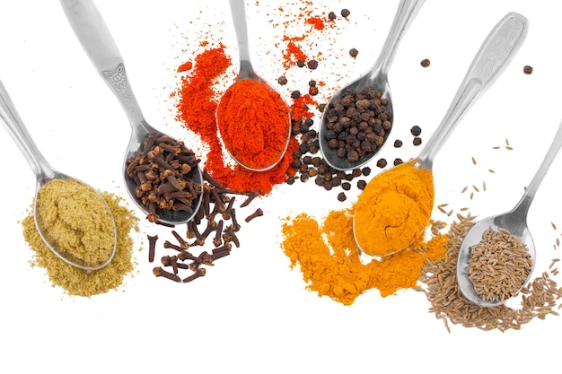 Indian spices in spoons isolated on white background