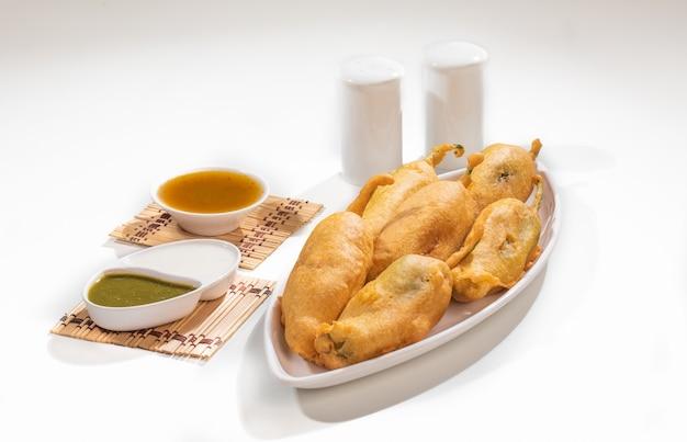 Индийская уличная жареная еда острый перец чили пакора, подаваемый с соусом и чатни, также известный как мирчи баджи, мирчи вада, мирчи бада, котлета чили или чили баджи это популярные закуски к чаепитию из индии