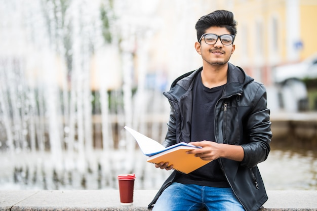 通りの噴水のそばに座って本の山を保持しているインドの学生男