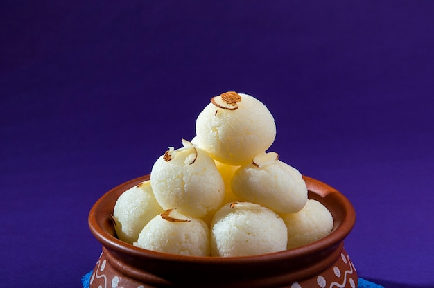 Indian sweet or dessert - rasgulla, famous bengali sweet in clay bowl with blue napkin on violet background