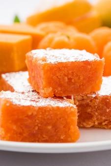 Indian sweet food orange burfi or orange cake or santra burfi in hindi, favourite festival food from central india